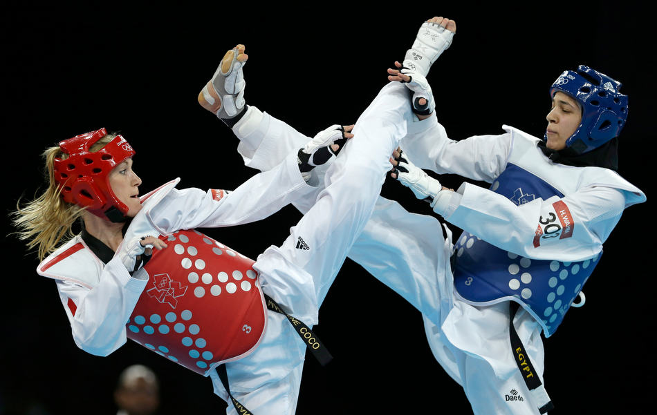 Egypt's Hedaya Wahba fights France's Marlene Harnois (in red) during their quarterfinal round match in women's 57-kg taekwondo competition at the 2012 Summer Olympics, Thursday, Aug. 9, 2012, in London. (AP Photo/Ng Han Guan)
